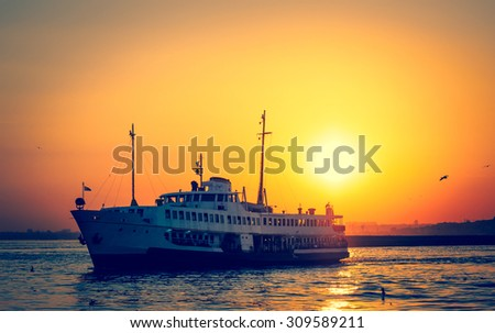 Silhouettes of turkish steamboat in Istanbul with seagulls at golden sunset. Old passenger ship of seascape Istanbul on evening. - stock photo