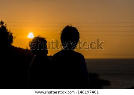 silhouettes of two boys looking at sunset - stock photo