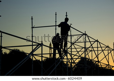 Silhouettes of two builders constructing something in the evening - stock photo