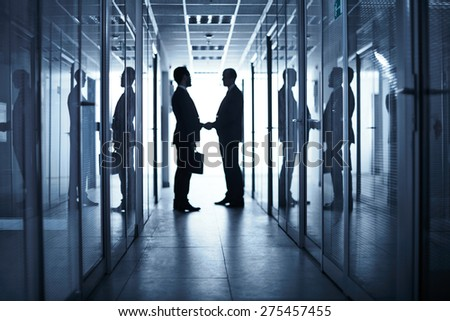 Silhouettes of two business partners handshaking in corridor of office building after negotiations - stock photo