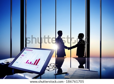 Silhouettes Of Two Businessmen Shaking Hands Together In A Board Room - stock photo