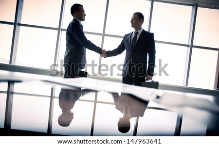 Silhouettes of two businessmen standing by the window and handshaking - stock photo