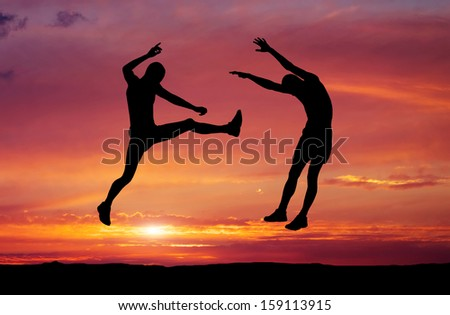 Silhouettes of two fighters on sunset fiery background. Battle at sunset. Kick in the air at the opponent's body.  - stock photo
