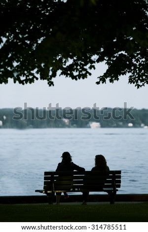 Silhouettes of two friends sitting on bench by the water talking. - stock photo