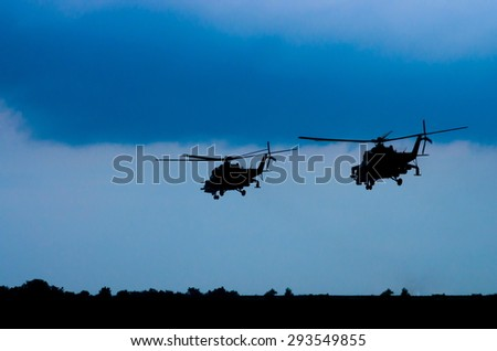 silhouettes of two helicopters