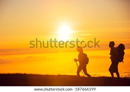 Silhouettes of two hikers with backpacks walking at sunset. Trekking and enjoying the sunset view from mountain top above the clouds. - stock photo