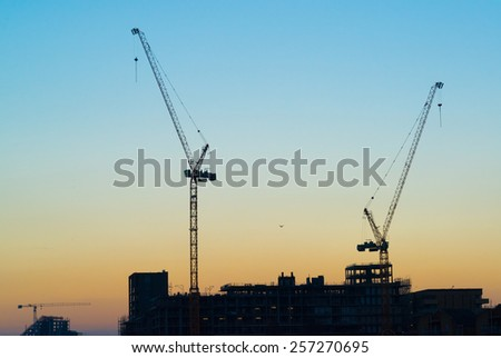 Silhouettes of two massive construction cranes with sky at sunset in the background. - stock photo