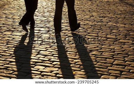 Silhouettes of two men walking - stock photo