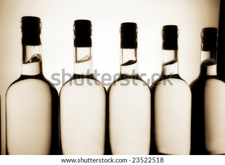 Silhouettes of white wine bottles on a production line - stock photo