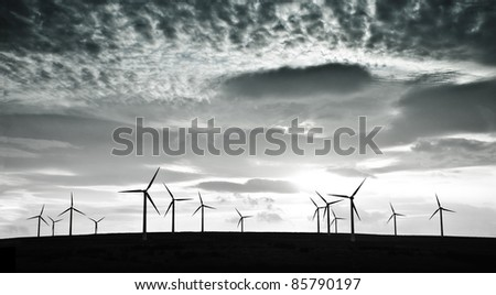Silhouettes of wind turbines against dramatic clouds - stock photo