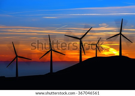 Silhouettes of Wind Turbines at Sunset / Five silhouettes of wind turbines in mountain with a beautiful sunset  - stock photo
