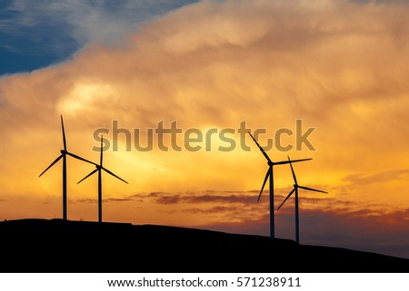 Silhouettes of wind turbines in the wind farm, amid fiery sunset