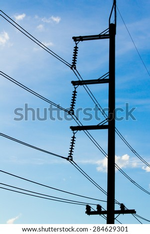 Silhouettes of wires and electric post on blue sky - stock photo