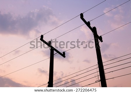 silhouettes of wires and electric post on sunset - stock photo