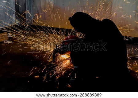 Silhouettes of Worker and sparks of bonfire while grinding iron - stock photo