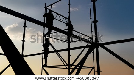 Silhouettes of workers on a scaffolding