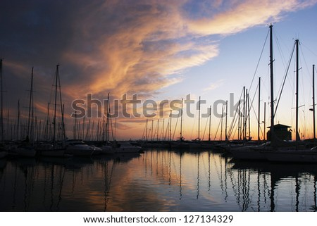 silhouettes of yachts in marina with magical sky - stock photo