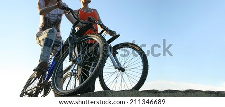 silhouettes of young activity Couple friends of two bicyclists on brink rock looks at summer sunset sky background in love ride bicycles along beach horizon No face Copy space for inscription - stock photo