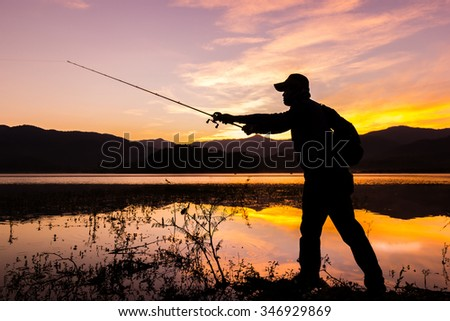 Silhouettes of young Asia man fishing on the lake early in the morning before sunrise - stock photo