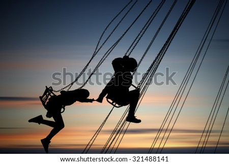 silhouettes of young girls having fun on carousel