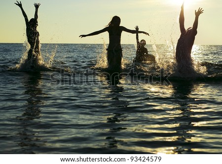 Silhouettes of young group of people jumping in ocean at sunset - stock photo