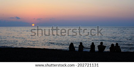 Silhouettes of young group of people  on the sunset near the sea - stock photo