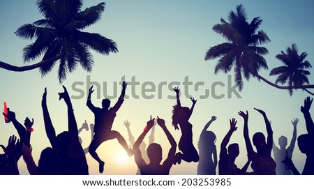 Silhouettes of Young People Celebrating on a Beach - stock photo