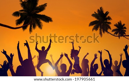 Silhouettes of Young People Partying on a Beach - stock photo