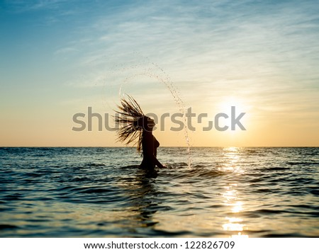 Silhouettes of young woman jumping in ocean at sunset - stock photo
