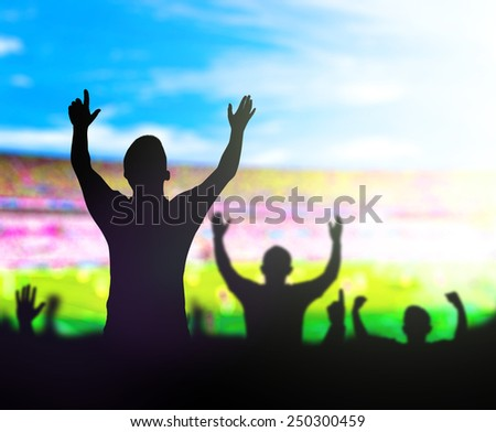 Silhouettes people raising hands over blurred stadium and blue sky background. - stock photo