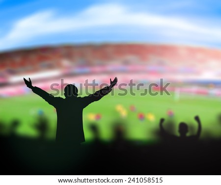 Silhouettes people raising hands over stadium. - stock photo