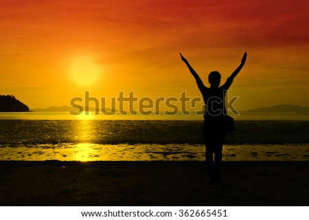 Silhouettes, strong confidence woman open arms under the sunrise at seaside - stock photo