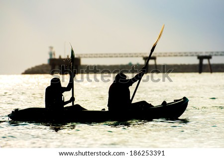 Silhouettes two people rowing on a sea - stock photo