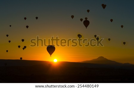 Silhouetts of hot balloons in morning sunrise and a mountain Erciyes. Cappadocia, Turkey - stock photo