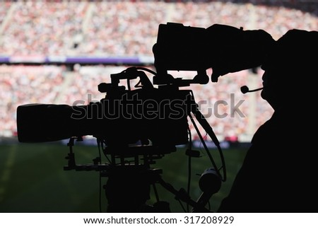 silhoutte of a camera man in a stadium - stock photo