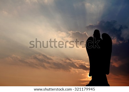 Silhoutte of an angel against a candy colored sunset sky. - stock photo