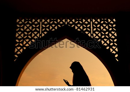 silhoutte of muslim woman praying during fasting holy month of ramadan - stock photo