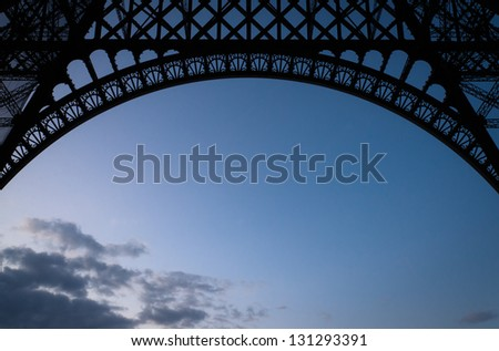 Silhoutte of the the underside skirt of the Eiffel Tower at dusk. - stock photo