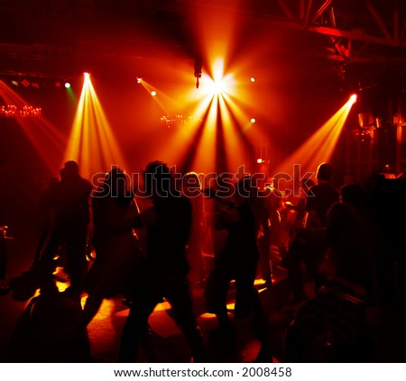 Silhouttes of dancing people in a disco - stock photo