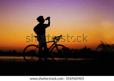 silhuette mountain bicycle rider drinking water at lake side against sunset - stock photo
