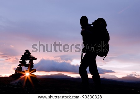 Silhuette of a Hiker with Backpack at Sunrise - stock photo