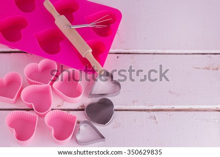Silicone molds for baking in the form of heart and tools for baking cookies, muffins and cake on a white wooden background. - stock photo