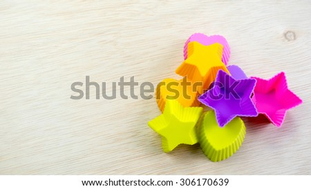 Silicone molds with starry and love shapes of different colors on a wooden surface. Concept of funky bakery or utensils for young chef. Slightly de-focused and close-up shot. Copy space. - stock photo
