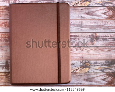 silk brown cover note book on wooden background - stock photo