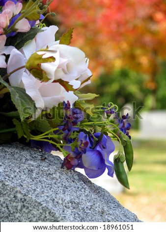 silk flowers on a cemetery grave headstone - stock photo