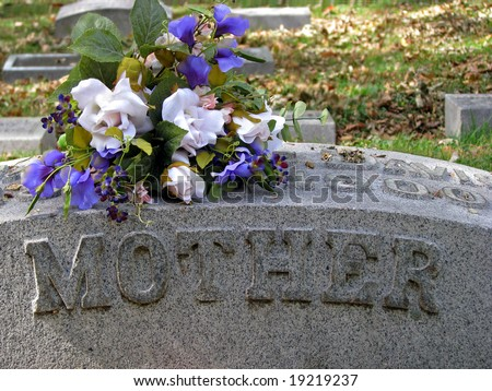 silk flowers on a cemetery grave headstone mother - stock photo