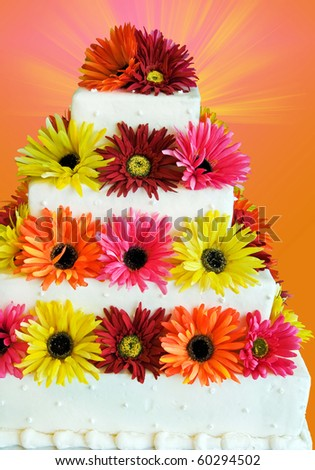 silk flowers on tiered cake - stock photo