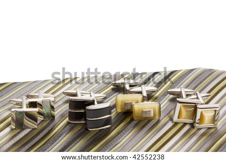 silk tie and cufflinks are posed on a nutral background - stock photo