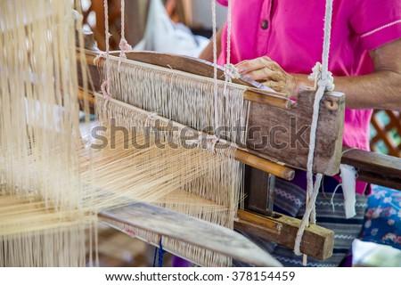 Silk weaving on loom. - stock photo