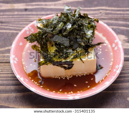 Silken tofu with sesame oil decorate, cold bean curd, soybean with seaweed in bowl on wooden background - stock photo